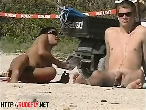 warm babes filmed lying on a nudist beach